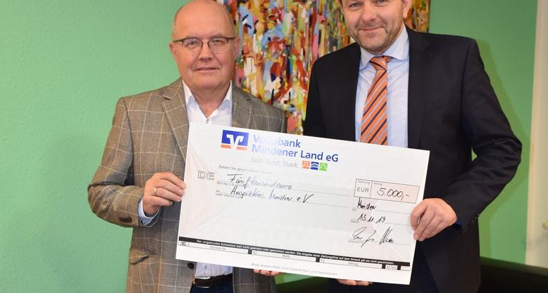 Ein symbolischer Scheck wechselt den Besitzer von Peter Scherf, Volksbank Mindener Land (re.) zu Helmut Dörmann, Hospizkreis
